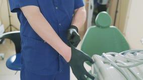 Il primo piano di un telaio potato colpo lento, il medico mette sopra i guanti medici sulle sue mani, aspettanti il suo paziente stock footage