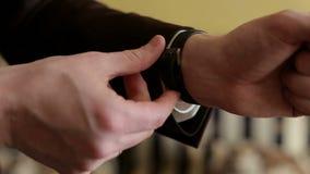 Il primo piano di un uomo fissa l'orologio sulla sua mano video d archivio