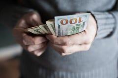Il primo piano di un uomo passa il conteggio delle note del dollaro Immagine Stock
