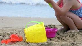 Il primo piano di una costruzione della ragazza fortifica nella sabbia stock footage