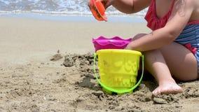 Il primo piano di una costruzione della ragazza fortifica nella sabbia video d archivio