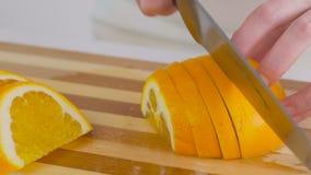 Il primo piano di una donna taglia un'arancia su un tagliere stock footage