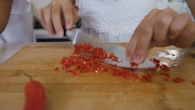 Il primo piano di una femmina passa il taglio del pepe rovente sul tagliere a casa nella cucina Le mani femminili sta tagliando i stock footage