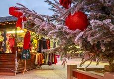 Il primo piano di una palla di Natale che appende su un albero nevoso con il Natale commercializza i chalet nel backgr Fotografia Stock Libera da Diritti