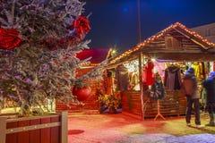 Il primo piano di una palla di Natale che appende su un albero nevoso con il Natale commercializza i chalet nel backgr Immagine Stock Libera da Diritti