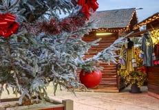 Il primo piano di una palla di Natale che appende su un albero nevoso con il Natale commercializza i chalet nel backgr Immagine Stock