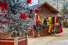 Il primo piano di una palla di Natale che appende su un albero nevoso con il Natale commercializza i chalet nel backgr Fotografia Stock