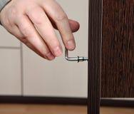 Il primo piano di una vite della mano ha avvitato la chiave esagonale, montante il furnitur Fotografia Stock