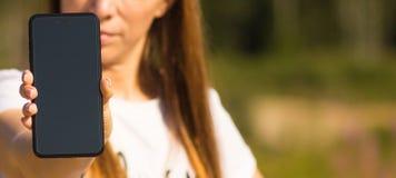 Il primo piano di uno smartphone, una ragazza sta tenendo un telefono in sua mano Fotografia Stock Libera da Diritti