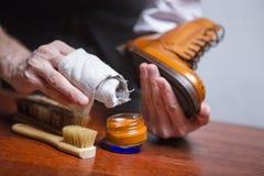 Il primo piano di uomo le mani con gli strumenti di pulizia che lucidano Tan Derby Boots fotografie stock