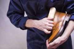 Il primo piano di uomo le mani con la spazzola di pulizia che compone Derby Boots premio immagini stock