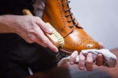 Il primo piano di uomo le mani con la spazzola di pulizia usata per il polacco della Tan High Derby Boots immagine stock libera da diritti