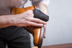 Il primo piano di uomo le mani con il panno di pulizia usato per il polacco della Tan High Derby Boots Contro Grey fotografie stock libere da diritti