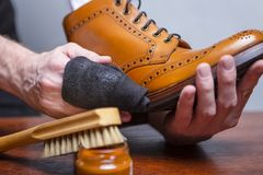 Il primo piano di uomo le mani con il panno di pulizia usato per il polacco e la scrematura della Tan High Derby Boots fotografia stock libera da diritti