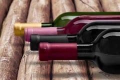 Il primo piano di vino scuro imbottiglia la fila su di legno Fotografia Stock
