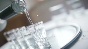 Il primo piano di vodka ha versato in un vetro di colpo archivi video