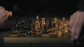 Il primo piano, due uomini gioca il gioco di scacchi alla notte archivi video