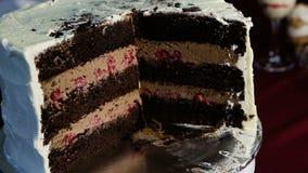 Il primo piano ha affettato il grande dolce di cioccolato con caramello e la ciliegia