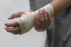 Il primo piano ha bendato il dolore del ` s degli uomini del polso la sua mano dopo lavoro immagini stock