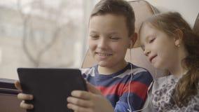 Il primo piano ha fatto di giovani ragazzo e ragazza che attraversano in bus through la città, guardando il film sulla compressa  stock footage