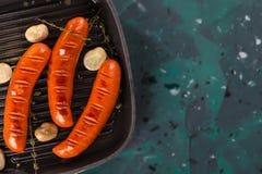 Il primo piano ha fritto la salsiccia in una padella, con le erbe e le spezie Fuoco selettivo fotografia stock libera da diritti