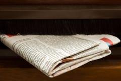 Il primo piano ha sparato del giornale che viene nella cassetta postale Fotografie Stock Libere da Diritti