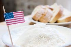 Il primo piano ha sparato della bandiera americana e della farina in un piatto Fette di pane sui precedenti Immagini Stock Libere da Diritti