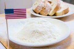 Il primo piano ha sparato della bandiera americana e della farina in un piatto Fette di pane sui precedenti Fotografia Stock