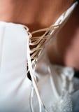 Il primo piano ha sparato della donna nella retrovisione del corsetto bianco Immagine Stock