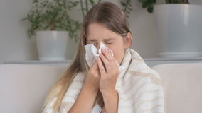 Il primo piano ha sparato della giovane donna che soffre dall'allergia che starnutisce in fazzoletto di carta stock footage