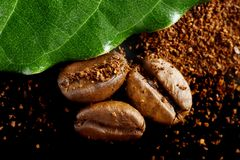 Il primo piano ha sparato della polvere del caffè, i fagioli con la foglia verde sul nero Fotografia Stock