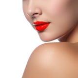 Il primo piano ha sparato delle labbra della donna con rossetto rosso lucido Immagine Stock