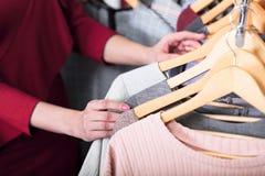 Il primo piano ha sparato delle mani della donna che scegliendo i nuovi vestiti Fotografia Stock Libera da Diritti