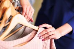 Il primo piano ha sparato delle mani della donna che scegliendo i nuovi vestiti Fotografie Stock