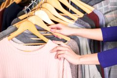 Il primo piano ha sparato delle mani della donna che scegliendo i nuovi vestiti Immagini Stock