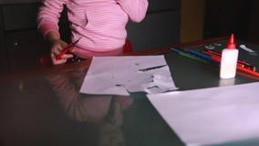 Il primo piano ha sparato delle mani sveglie del ` s della bambina nelle forme rosa di taglio del maglione da carta, tavola di ve archivi video