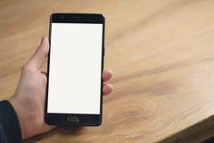Il primo piano ha sparato delle mani teenager femminili con lo smartphone alla tavola Fotografia Stock Libera da Diritti