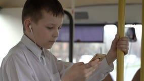 Il primo piano ha sparato di giovane ragazzo che attraversa in bus through la città Facendo uso dello smartphone ed ascolta music archivi video