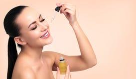 Il primo piano ha sparato di olio cosmetico che si applica sul fronte del ` s della giovane donna fotografia stock