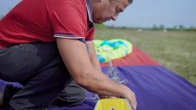 Il primo piano ha sparato di un professionista che fa i bagagli un paracadute in un campo vuoto stock footage