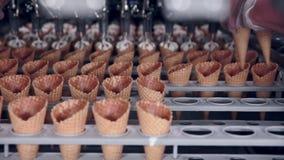 Il primo piano ha sparato di una cinghia commovente con i coni gelati e di un lavoratore che li prende Industria alimentare stock footage