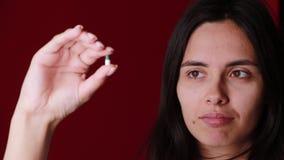 Il primo piano ha sparato di una mano che tiene le pillole di colore su fondo archivi video