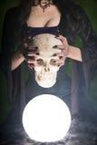 Il primo piano ha sparato di una strega con i chiodi lunghi che tengono il cranio umano fotografia stock