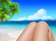 Il primo piano ha tonificato la foto delle gambe femminili esili che si abbronzano sulla spiaggia Immagini Stock Libere da Diritti