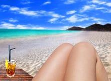 Il primo piano ha tonificato la foto delle gambe femminili esili che si abbronzano sulla spiaggia con il cocktail Fotografie Stock