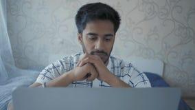 Il primo piano, indiano Guy Takes fuori dai punti ed esamina Pensively il monitor del computer portatile archivi video