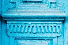 Il primo piano l'elemento del blu molte volte ha dipinto la porta d'annata di legno a doppia canna incrinata del secolo scorso co Fotografia Stock