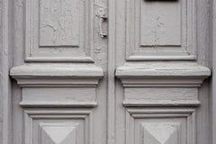 Il primo piano l'elemento di gray molte volte ha dipinto la porta d'annata di legno a doppia canna incrinata del secolo scorso co Fotografie Stock