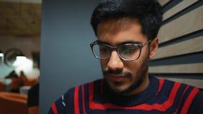 Il primo piano, la riflessione nei punti che un tipo indiano esamina le notizie si alimenta uno smartphone stock footage