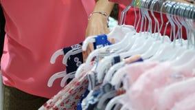 Il primo piano, mani femminili ha selezionato molti ganci con le attrezzature selezione ed acquisto dei vestiti nel deposito Acqu stock footage